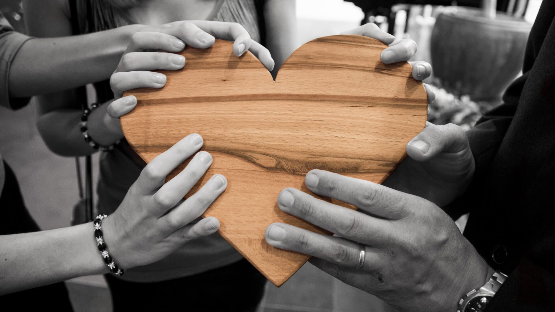 hands holding a wooden heart discussing how to connect with your customers