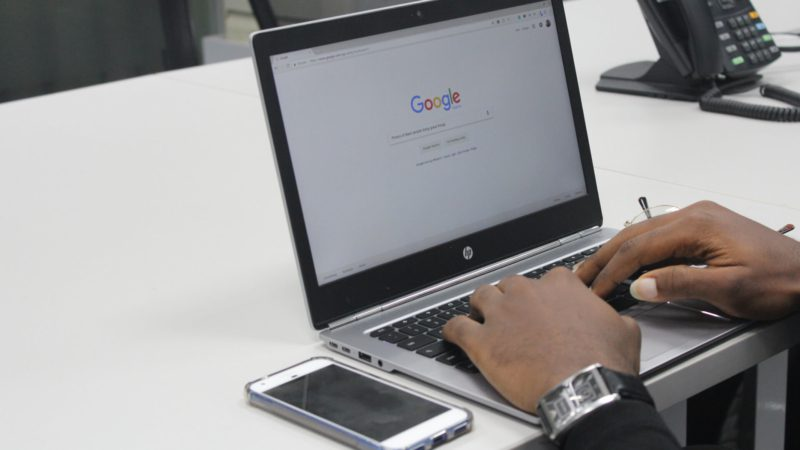 man google searching whether SEO works for small businesses on a laptop