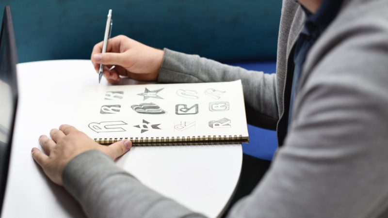 college student writing about 5 Best Practices When Starting a Logo Design