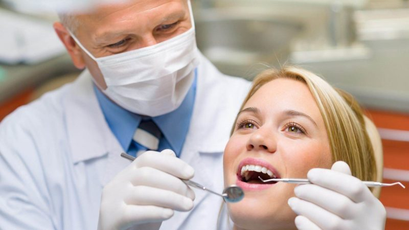 dentist with patient after getting more dental patients to his dental office