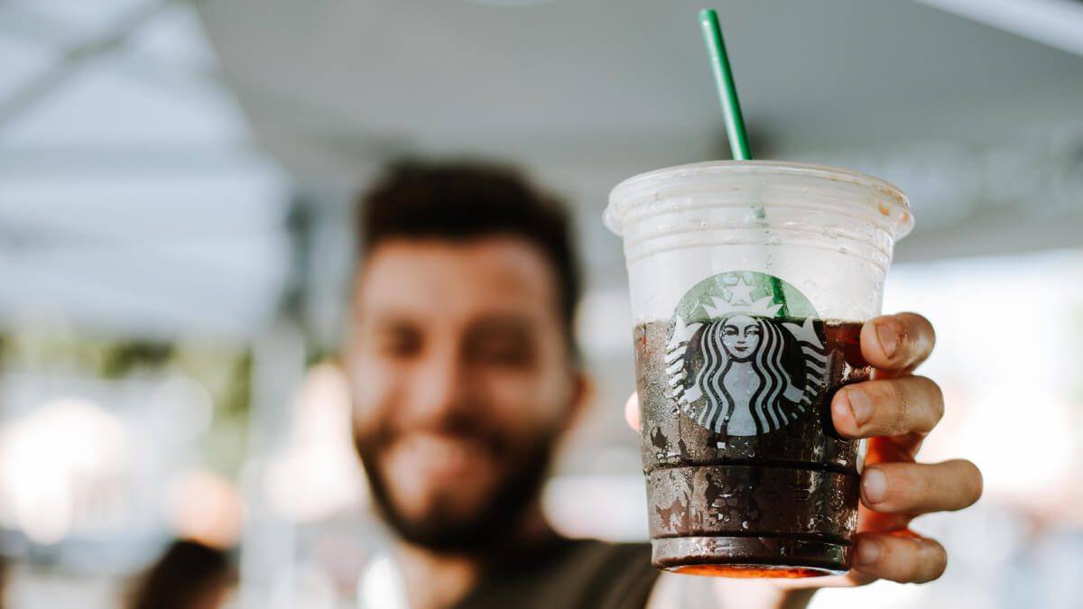 bearded man holding starbucks iced coffee in the summer