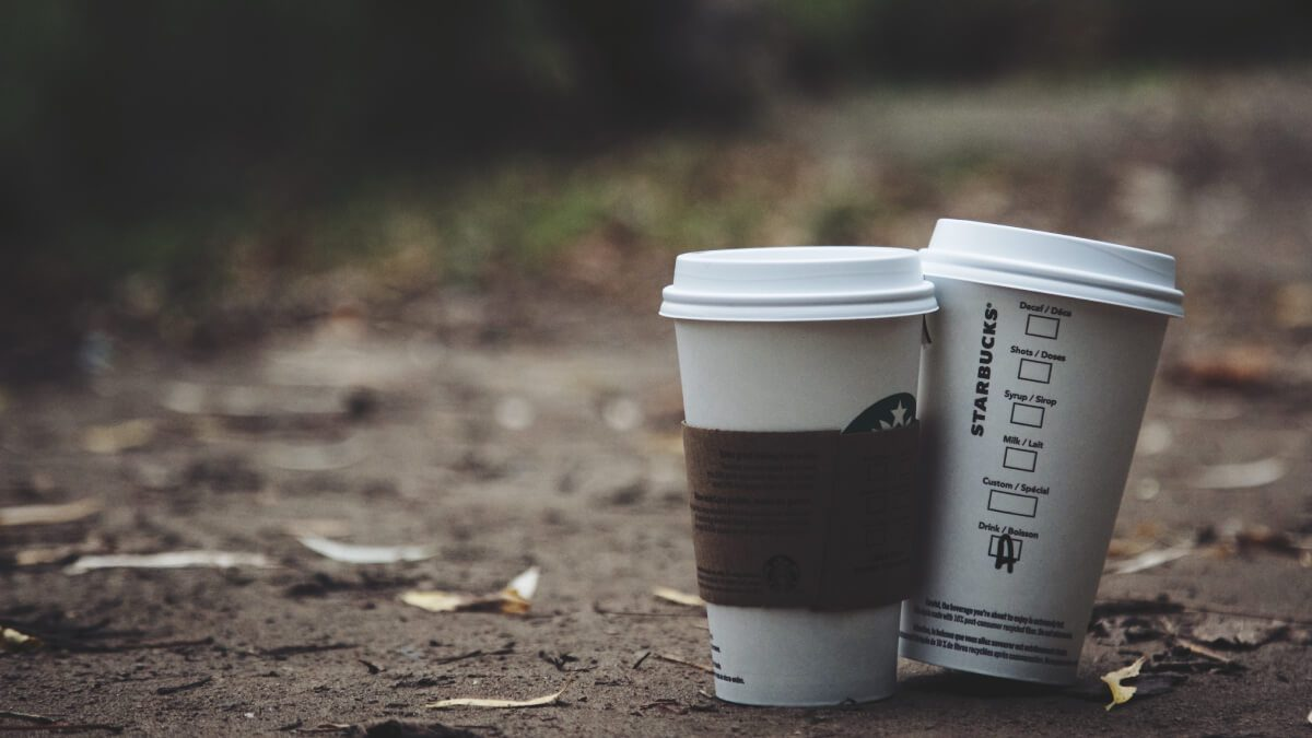 two starbucks coffees sitting in the fall leaves