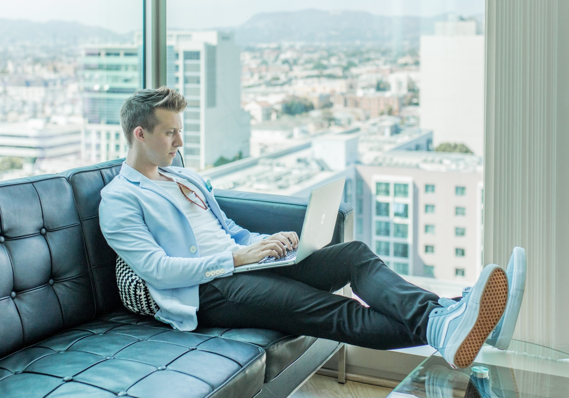young man in blue sports coat working on laptop