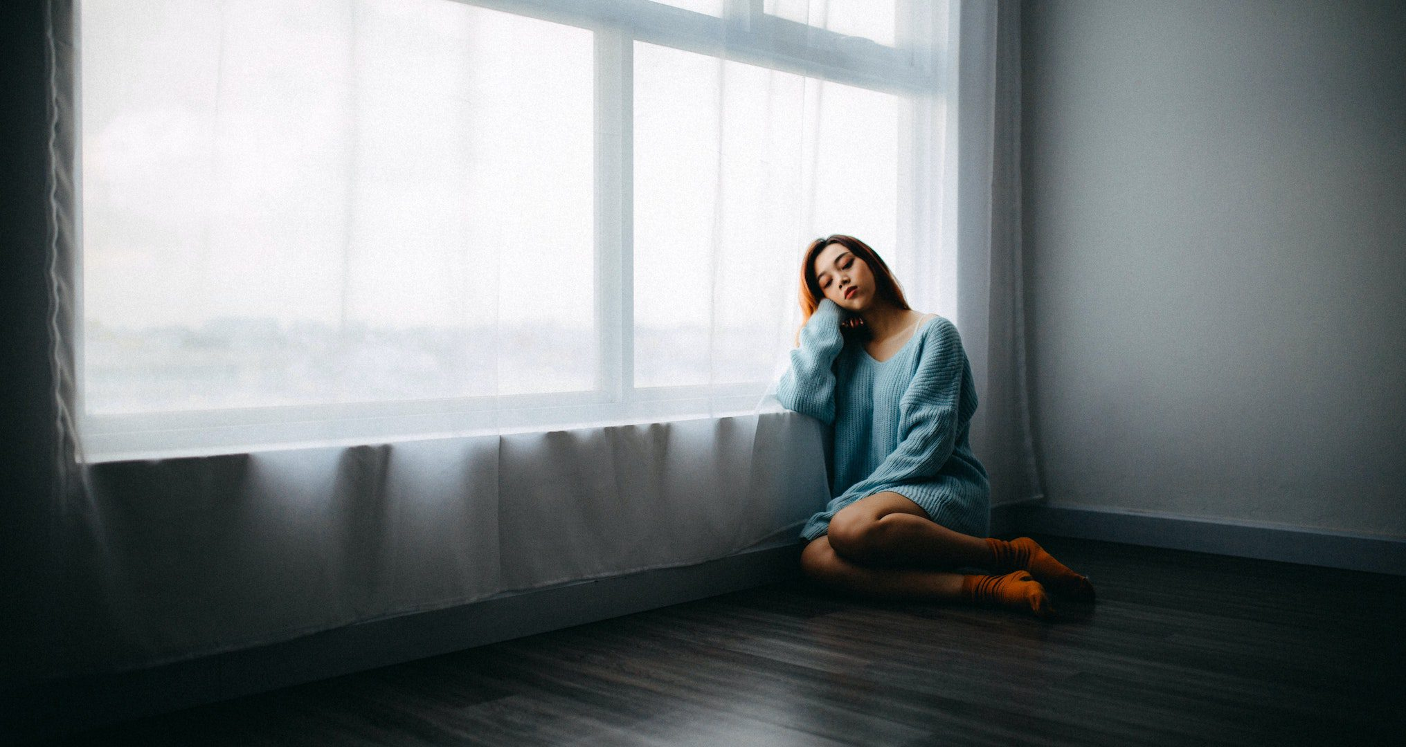 girl sitting on floor alone in a room