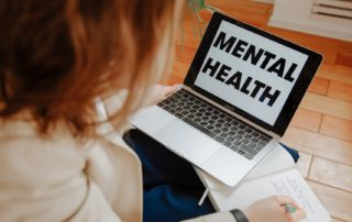 person using laptop with the words mental health on the screen