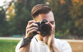 man holding a camera and taking pictures