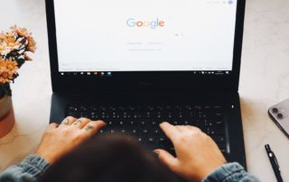 person working on laptop with google on the screen