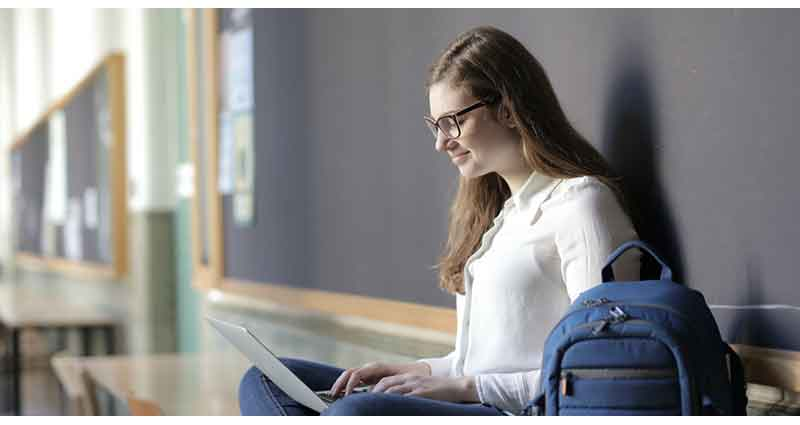 woman using laptop while-sitting-on-table near blue backpack