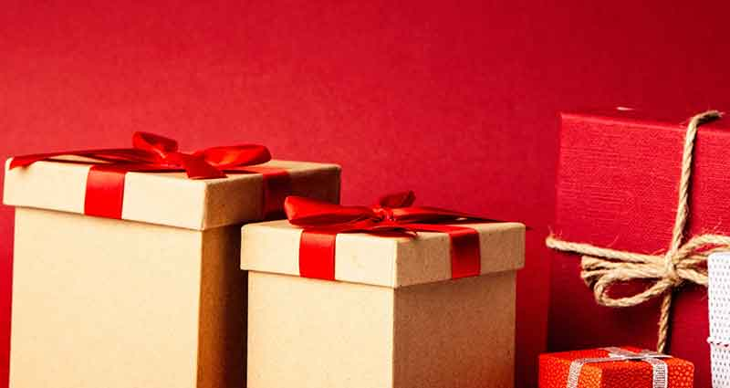 christmas presents wrapped in front of a red background