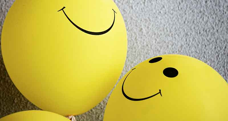 yellow balloons with happy faces on them